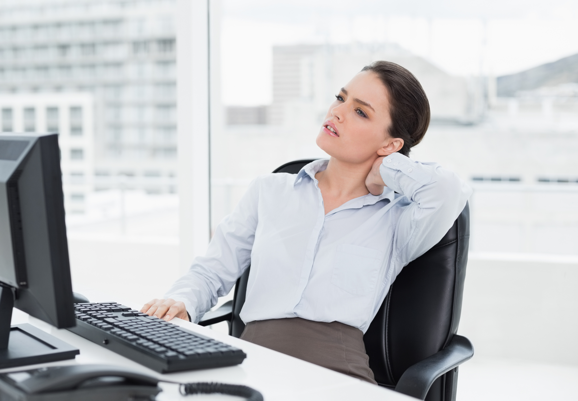 Young businesswoman with neck pain sitting at office desk